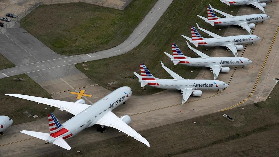 Des avions inutilisés sont stationnés le long d'une piste d'aéroport.