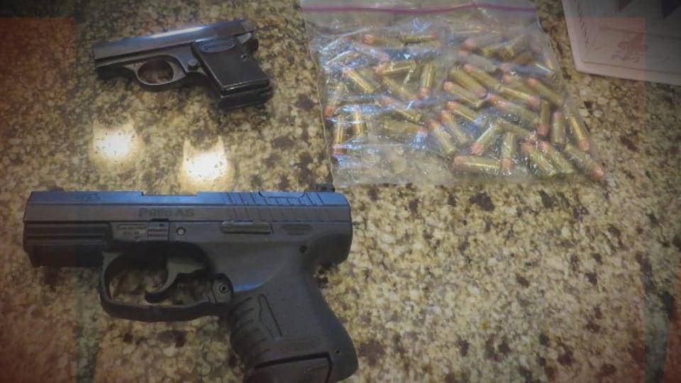 Deux armes à feu sont posées sur une table avec un sac de cartouches.