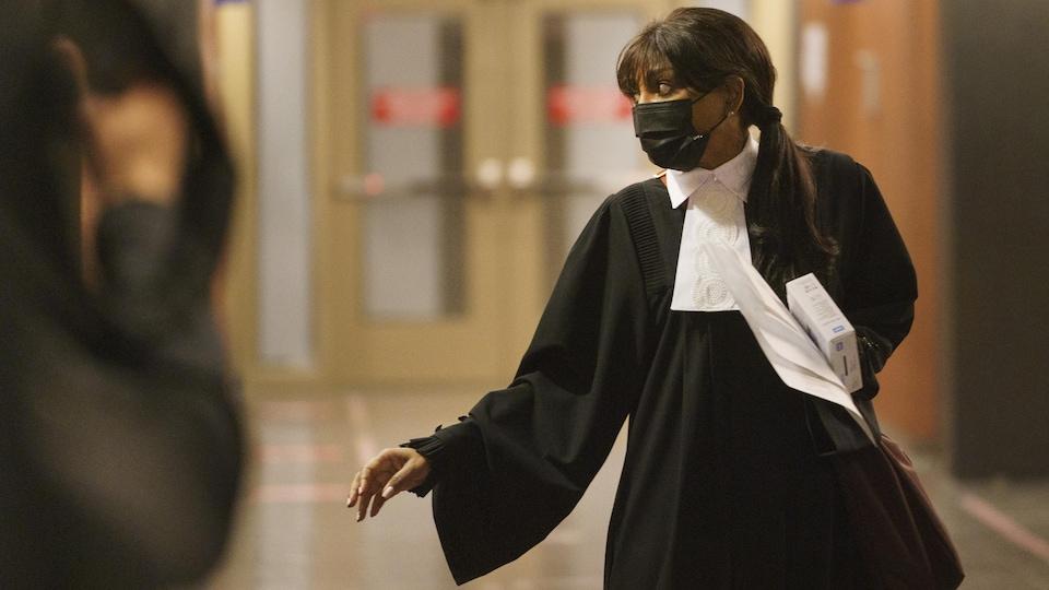 Une avocate tient un disque dur et des documents dans ses mains.