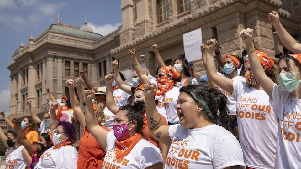 Un groupe de femmes sur les marches d'un édifice d'Austin au Texas lèvent le bras droit et scandent des slogans en faveur de l'avortement.