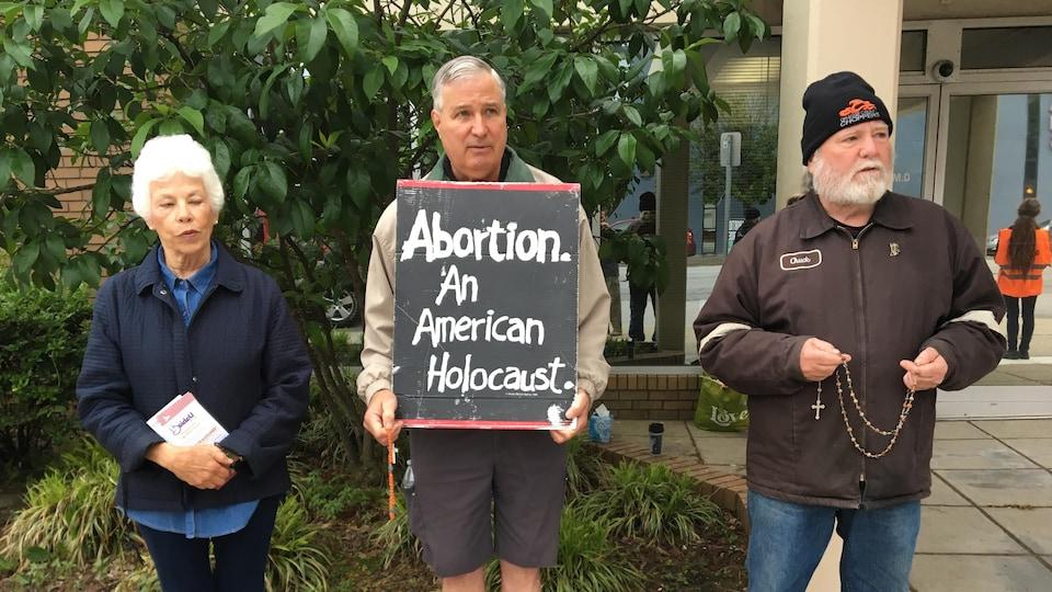 Trois manifestants, dont un qui tient une pancarte affichant «L'avortement. L'holocauste américain».