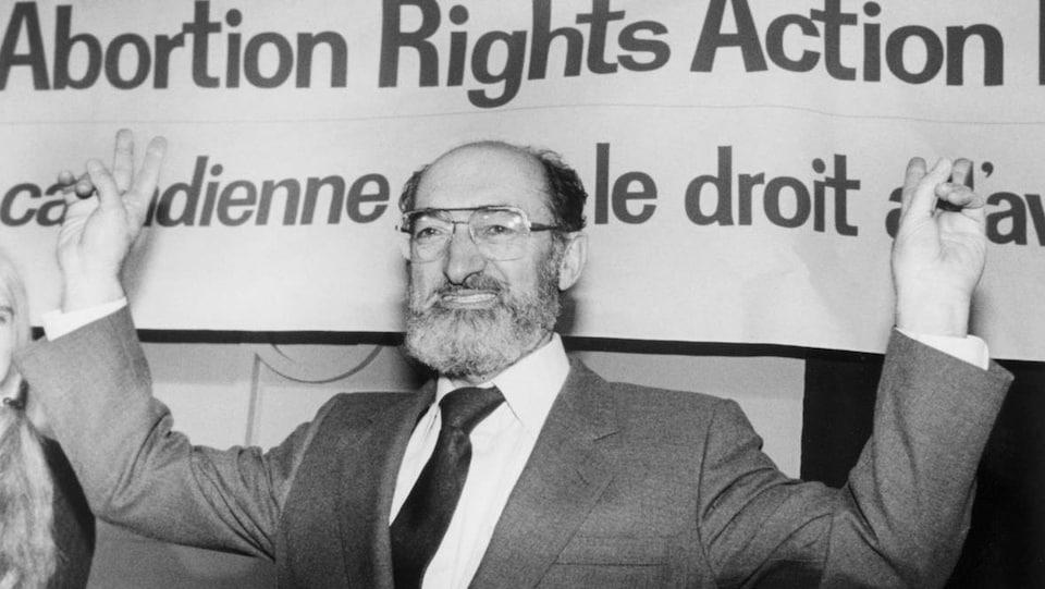 Le Dr. Morgentaler se tient devant une bannière pro-choix