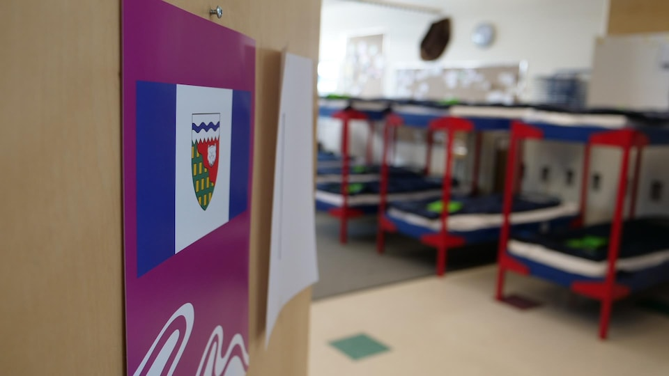 Par la porte entrouverte d'une salle de classe, on peut voir une rangée de lits superposés.