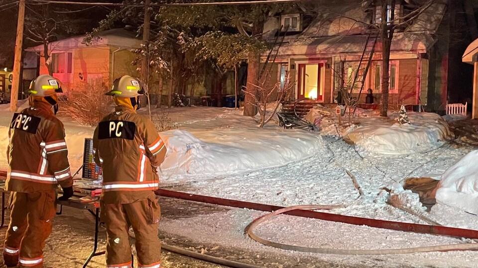 Des flammes sont visibles par la porte d'entrée de la maison.