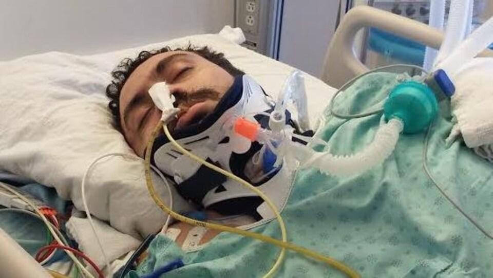 Un homme est couché sur un lit d'hôpital et intubé.