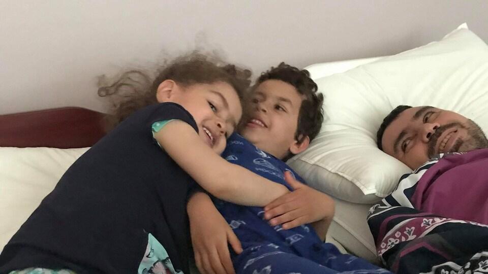 Un homme est entouré de ses enfants dans un lit.