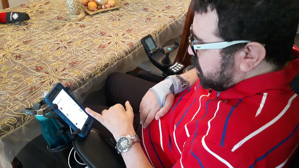 Assis dans un fauteuil roulant, un homme utilise son téléphone mobile.