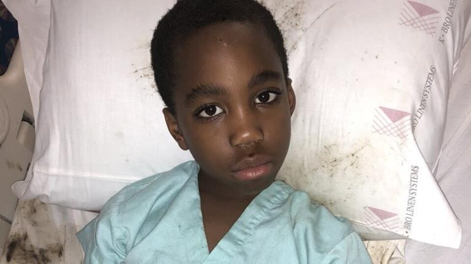 Photo d'un jeune garçon noir, la tête sur un oreiller.
