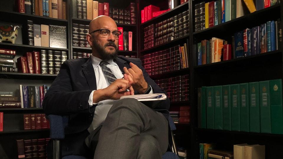 Un homme assis devant des étagères de livres durant une entrevue.