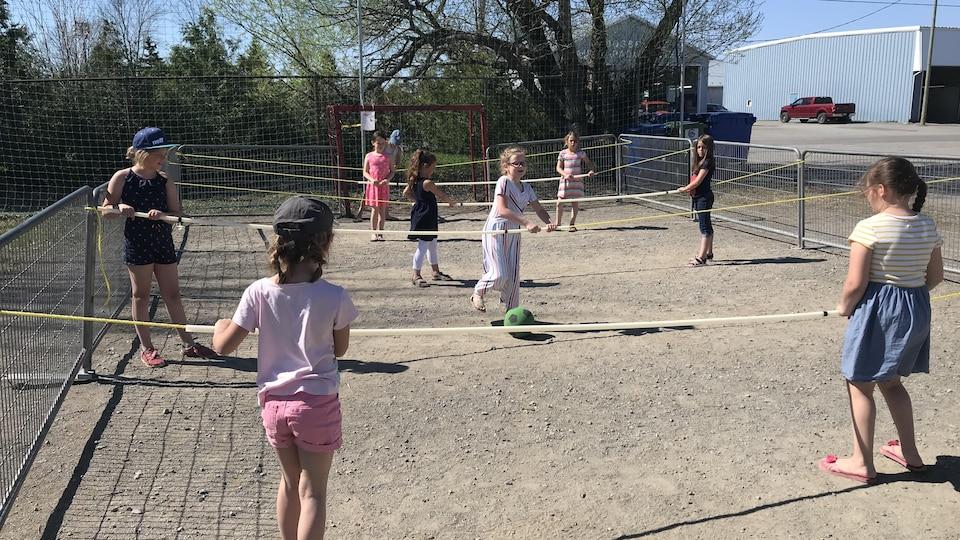 Des enfants sur un terrain tiennent des cordes et se passent un ballon.