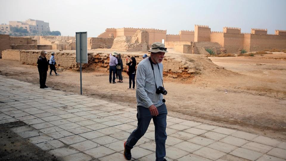 Des touristes marchent dans la cité de Babylone.