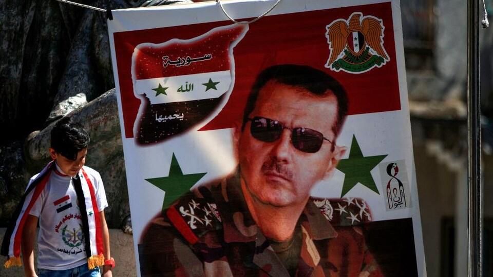 Un jeune garçon passe près d'une bannière sur laquelle figure le portrait de Bachar Al-Assad.