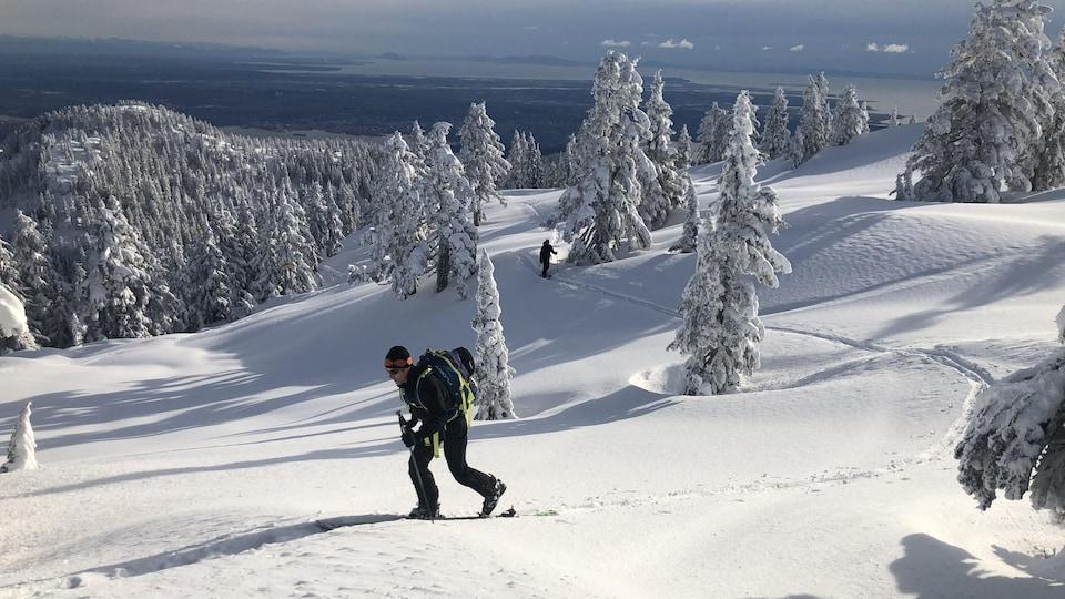 Un skieur de randonnée monte un sentier.