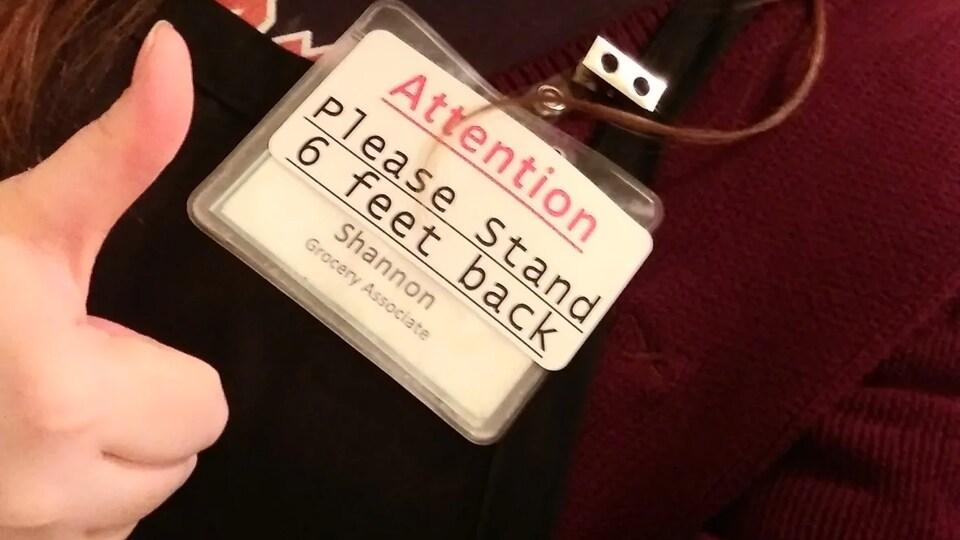 Un badge d'identification d'une employée demandant au client de se tenir à deux mètres de distance.