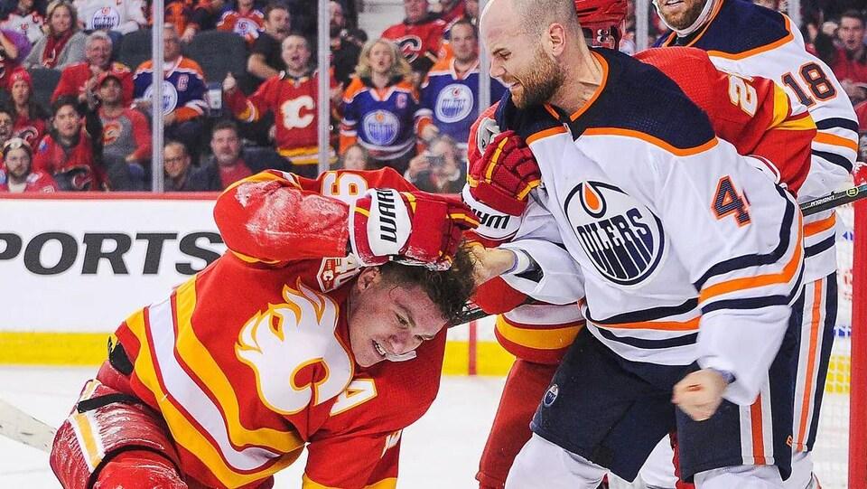 Zack Kassian s'apprête à frapper Matthew Tkachuk, qu'il tient par le collet. Matthew Tkachuk est agenouillé sur la glace.