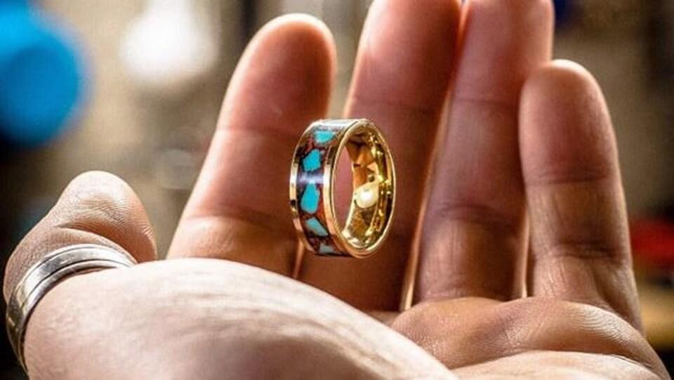 Une bague en or dans la paume de la main d'un homme.