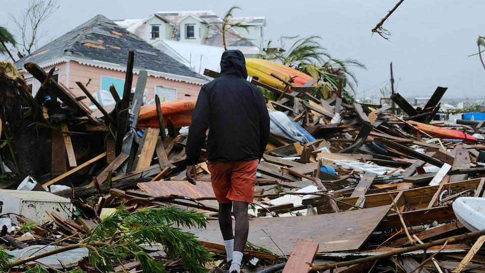 Un homme marche dans un tas de débris sous un ciel gris.