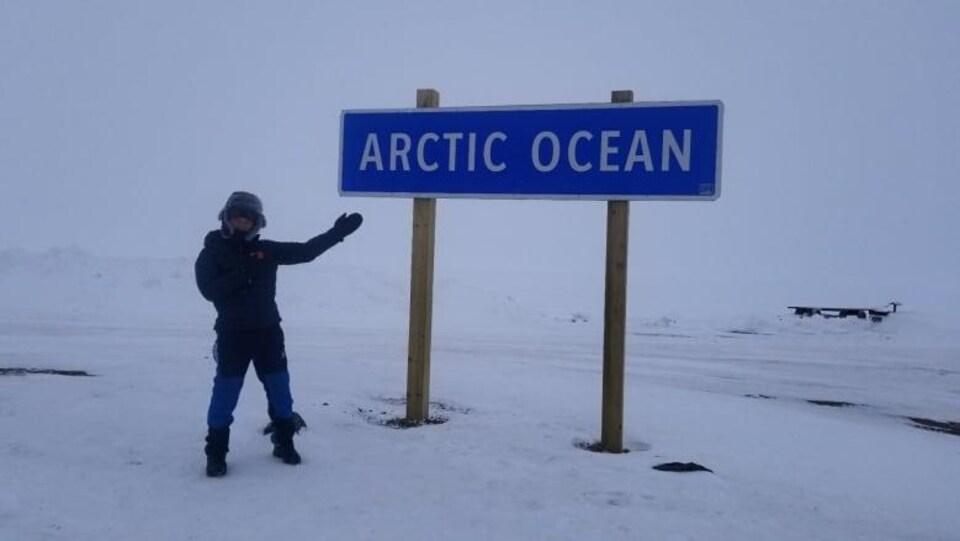 Bai Bin porte un manteau et se trouve debout sur la neige devant un grand panneau qui indique le nom de l'océan Arctique.