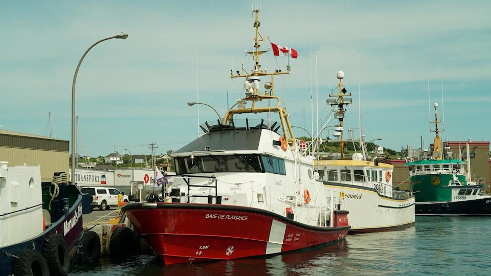 Trois bateaux, dont le Baie de Plaisance, aux couleurs blanches et rouges de la Garde côtière, sont accostés à un quai dans le port de Cap-aux-Meules.