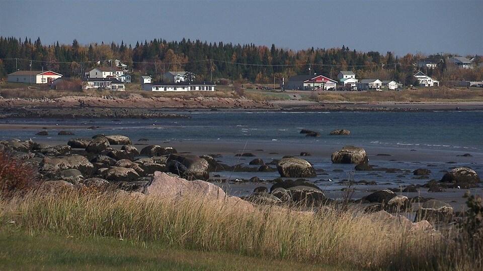 Des maisons au loin sur le bord de l'eau. Au premier plan des roches et de l'herbe.