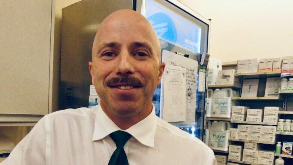Keith Bailey devant des étalages de médicaments