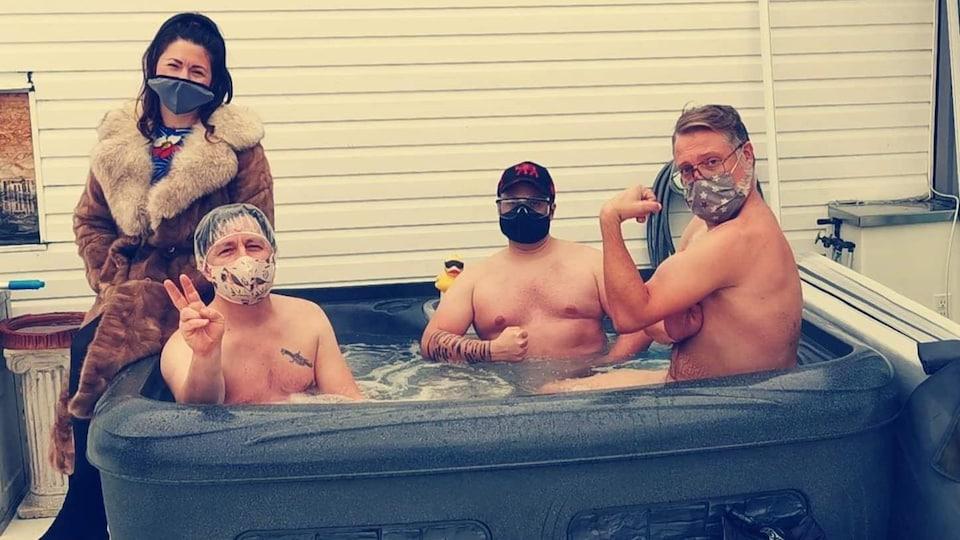 Trois hommes sont assis dans un spa et une femme s'ajoute à eux pour une photo officielle.
