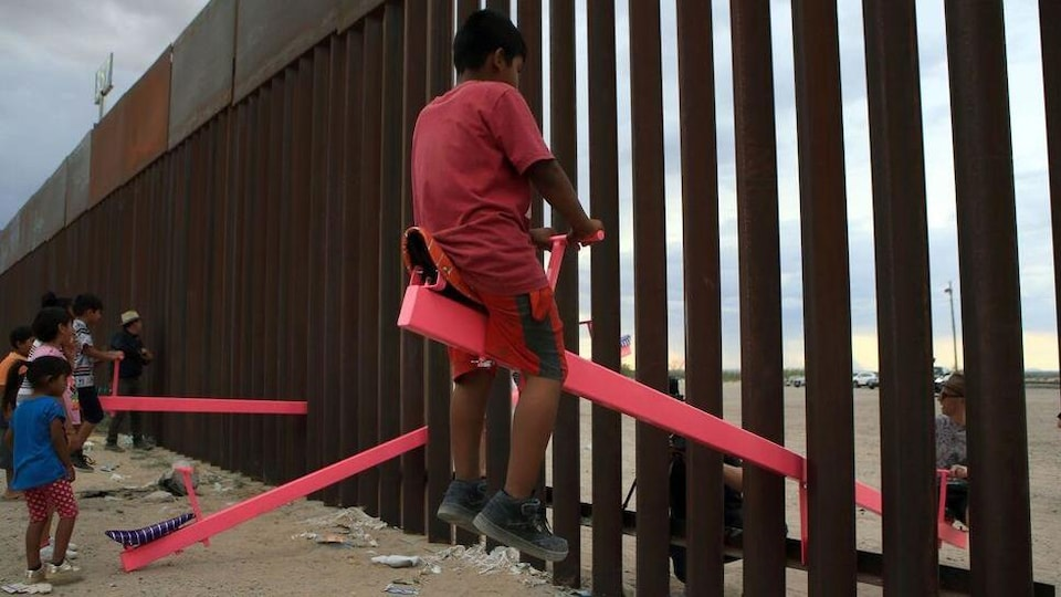 Des balançoires installées entre les barreaux du mur qui sépare les États-Unis du Mexique.