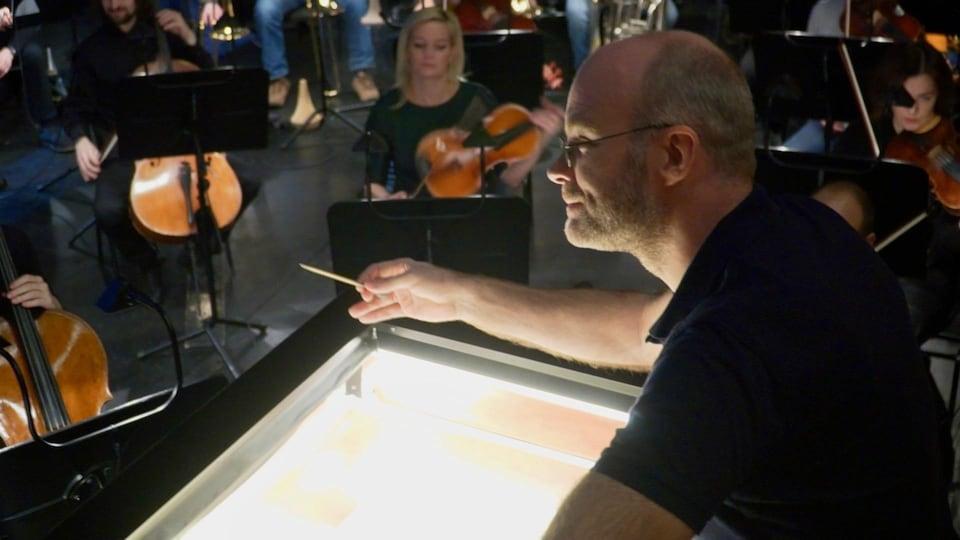 Un chef d'orchestre et des musiciens.