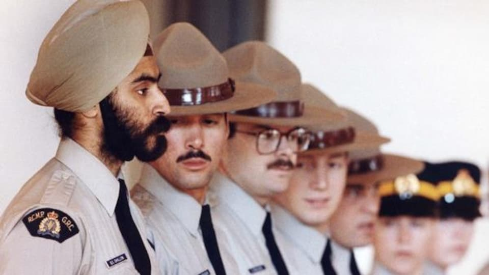 Le policier regarde droit devant lui, alors que ses collègues ont le regard fixé sur lui.