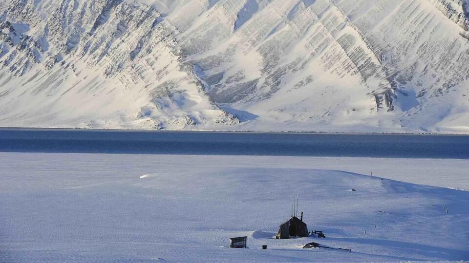 Une cabane en bois devant une montagne enneigée.