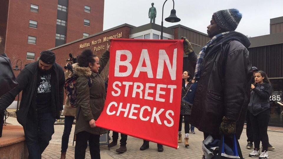Des manifestants exhibent une bannière «Ban Street Checks» le 30 mars 2019 devant une bibliothèque d'Halifax.