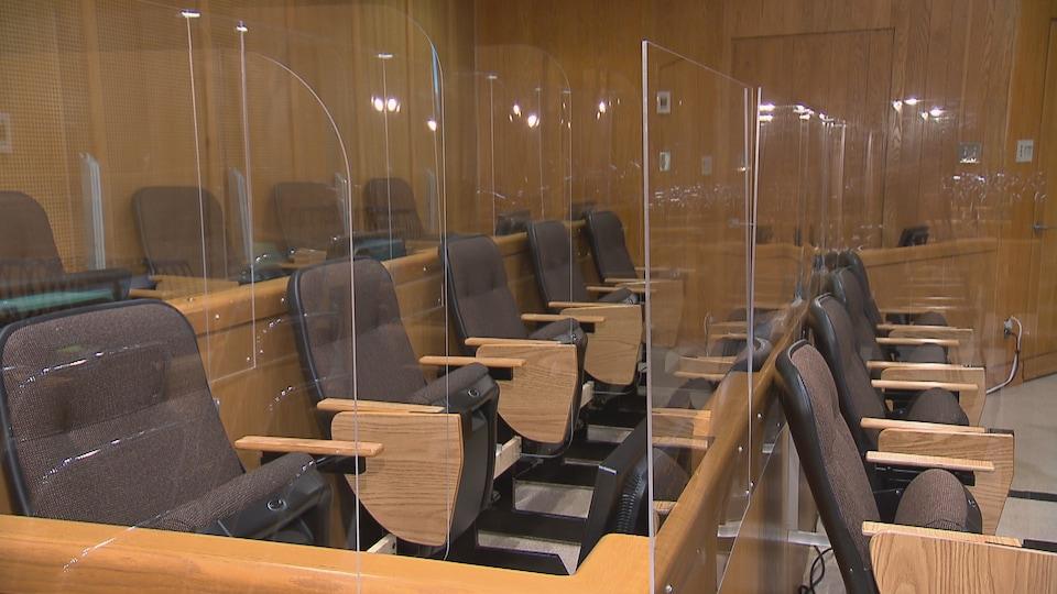 Les sièges bruns sont séparés par des panneaux de plexiglas.