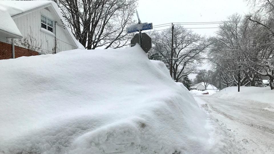 Photographie d'un banc de neige située sur un terrain privé d'un quartier résidentiel de Québec. Un panneau ARRÊT est presque entièrement dissimulé par la neige soufflée.