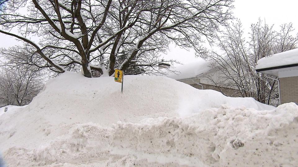 Une maison partiellement dissimulée par un banc de neige dans un quartier résidentiel de l'arrondissement Sainte-Foy–Sillery–Cap-Rouge, à Québec.