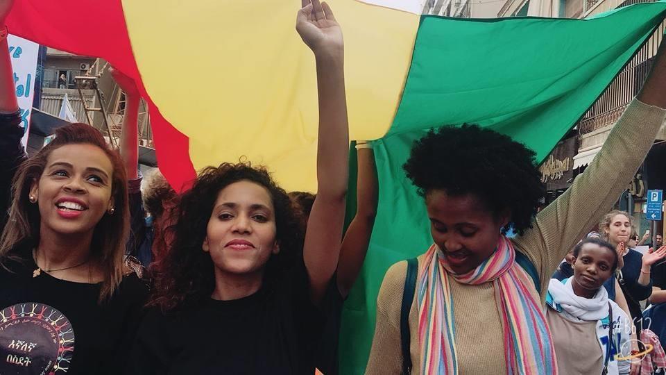 Des femmes migrantes manifestent en brandissant le drapeau éthiopien.