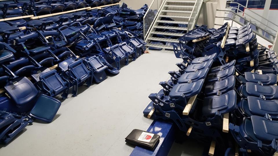 Des bancs sont dans les gradins d'un aréna.