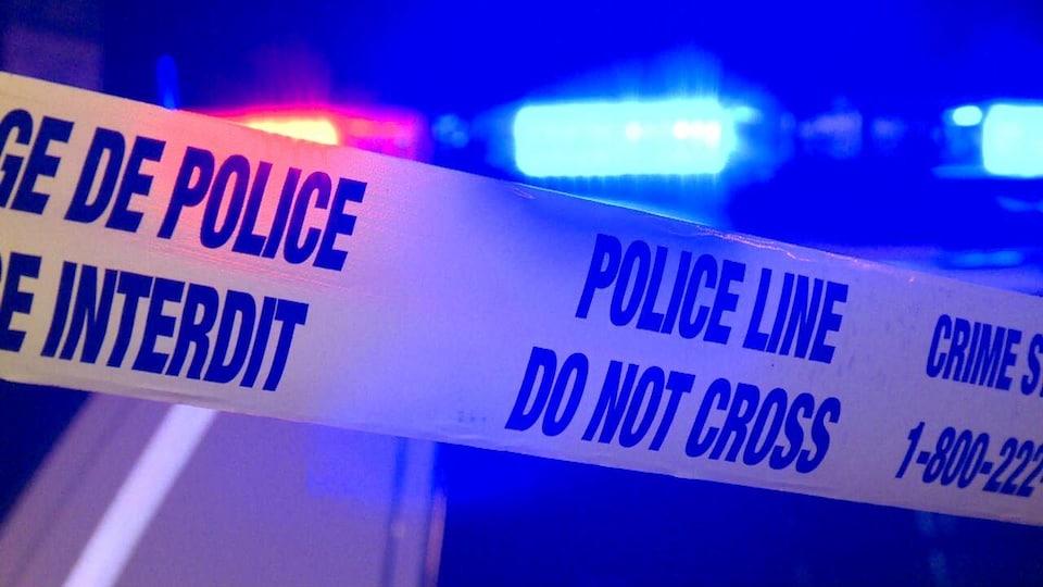 Banderole de police jaune devant une autopatrouille aux gyrophares allumés.