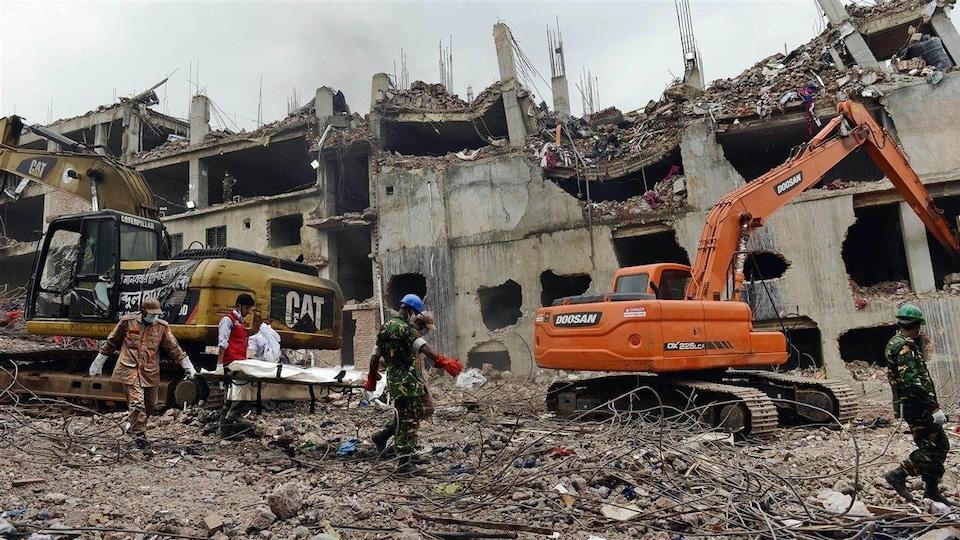 Les secouristes transportent le corps d'une victime découverte dans les décombres du Rana Plaza, deux semaines après son effondrement, au Bangladesh