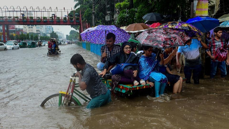 Des femmes et des hommes s'entassent sur un rickshaw