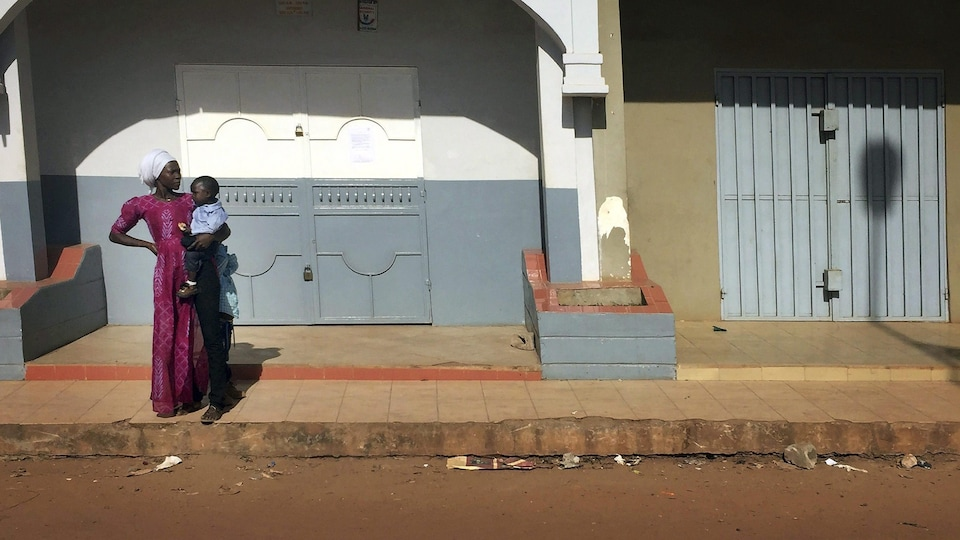 Une femme porte son enfant dans une rue de Banjul, capitale de la Gambie.