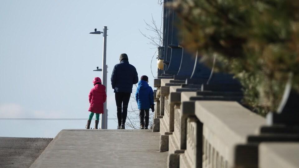 Trois piétons marchent sur le pont.