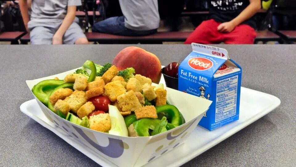 Un plateau avec une petite brique de lait, un lunch avec des croûtons, un poivron vert, des tomates, des brocolis, une pêche.
