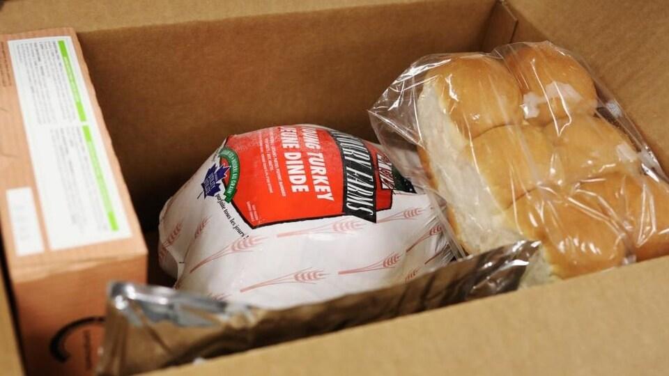 Une boîte qui contient, entre autres, des pains, de la dinde et une tarte.