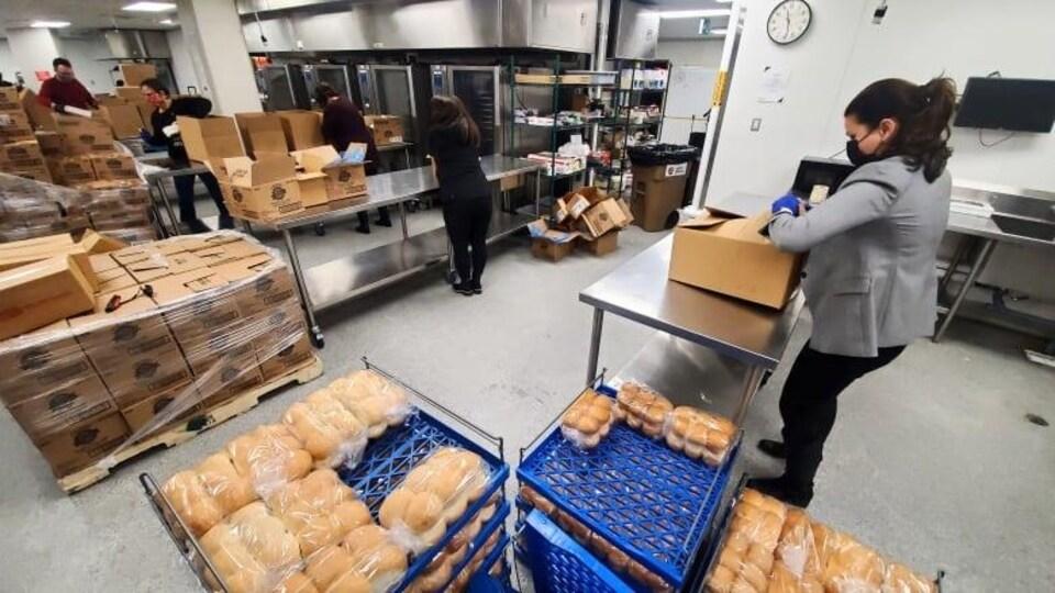 Plusieurs bénévoles remplissent ou emballent des boîtes de carton pour les Fêtes.