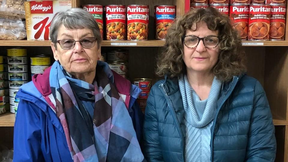 Deux femmes devant des étagères de boîtes de conserve.