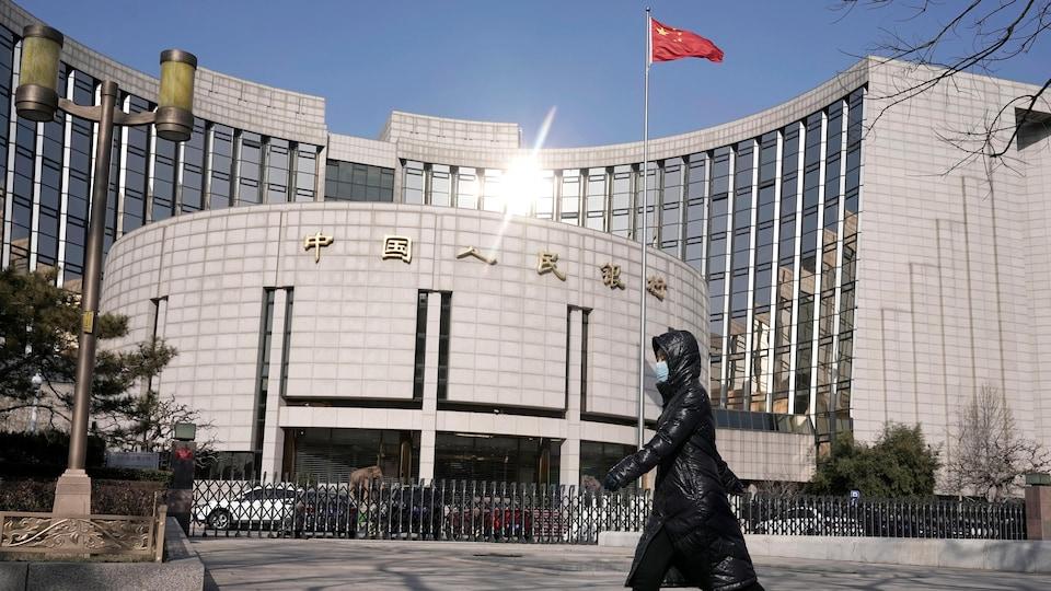 Une femme portant un masque passe devant l'immeuble d'un établissement bancaire chinois.