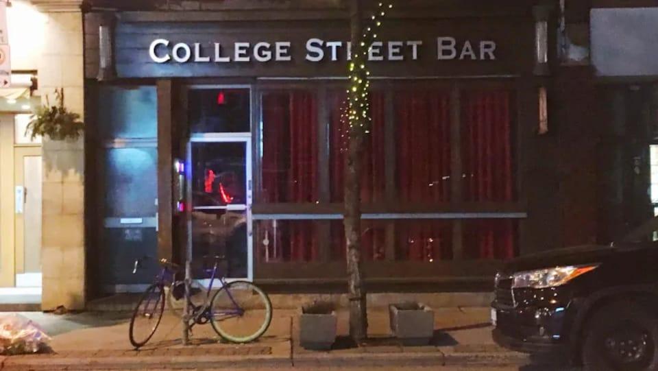 La façade d'un bar avec une enseigne sur laquelle est écrit : College Street Bar. La photo a été prise de nuit.