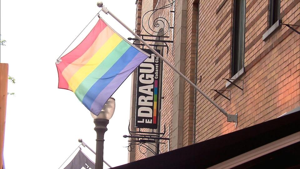 Un drapeau de la fierté qui flotte devant l'enseigne du bar Le Drague