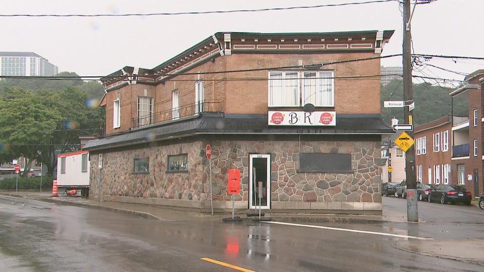 La façade d'un bar à l'angle de deux rues, sous un ciel pluvieux.