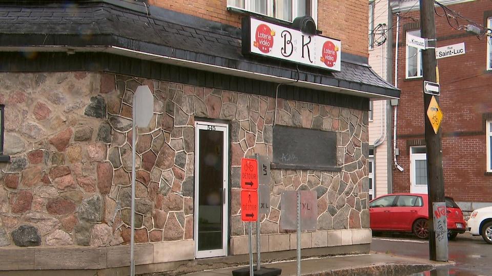 La façade d'un bar. On peut voir l'enseigne blanche où est écrit Bar Kirouac.